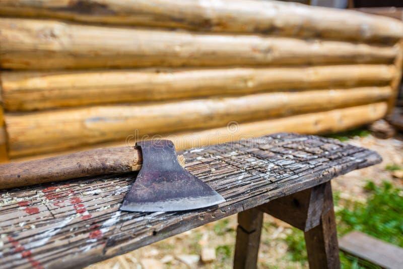 O interruptor inversor ou o machado de madeira são usados construindo a casa de madeira do pinho e das tiras da madeira serrada n fotos de stock