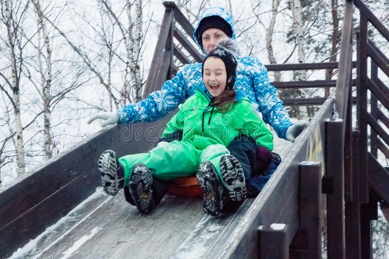 O inverno anda no ar fresco passeio da montanha russa no bolo de queijo Mamã e filha fotografia de stock