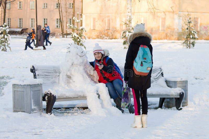 O inverno está vindo Duas meninas que fazem o selfie com um boneco de neve fotos de stock royalty free