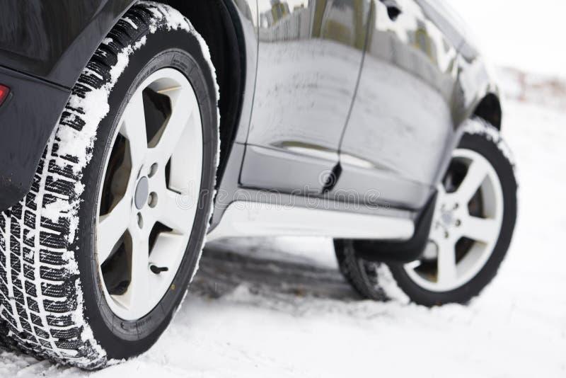 O inverno monta pneus as rodas instaladas no carro do suv fora imagem de stock