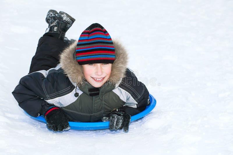 O inverno vestindo da criança de Beuatiful veste sledding na neve imagens de stock royalty free