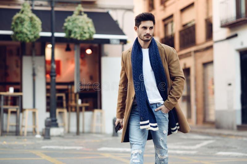 O inverno vestindo do homem novo veste-se com um smartphone em sua mão imagens de stock