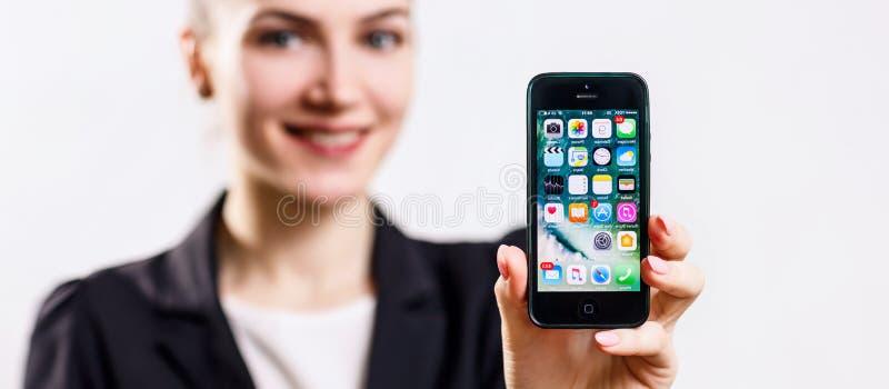 O iPhone preto 5 de Apple das posses da jovem mulher indica à disposição fotos de stock royalty free