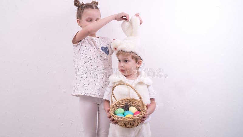 O irmão e a irmã comemoram a Páscoa O menino é vestido em um traje do coelho e guarda um korunzku com ovos da páscoa foto de stock royalty free