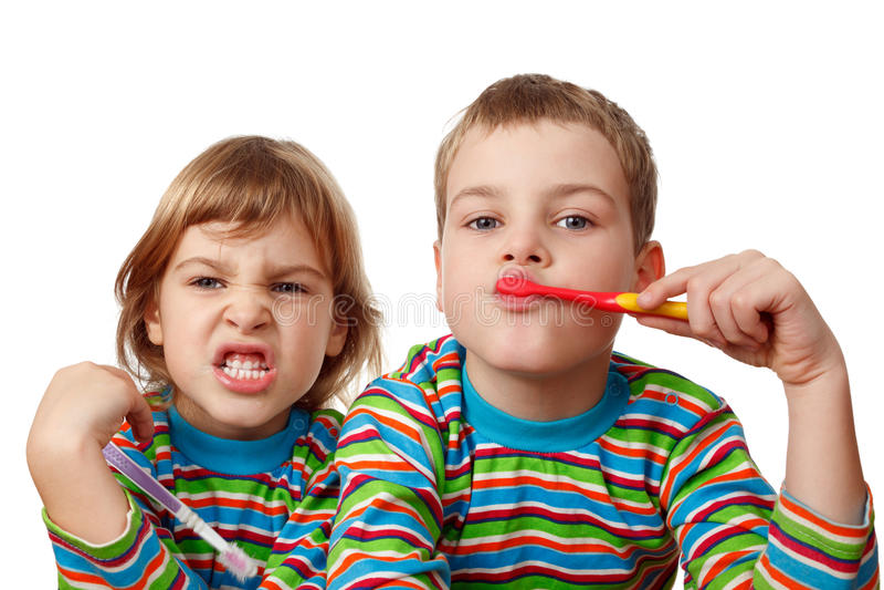 O irmão e a irmã nas camisas escovam seus dentes fotos de stock royalty free