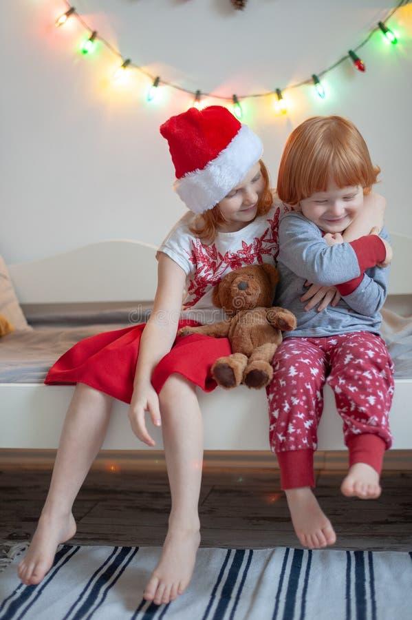 O irmão e a irmã sentam-se em uma cama fotografia de stock