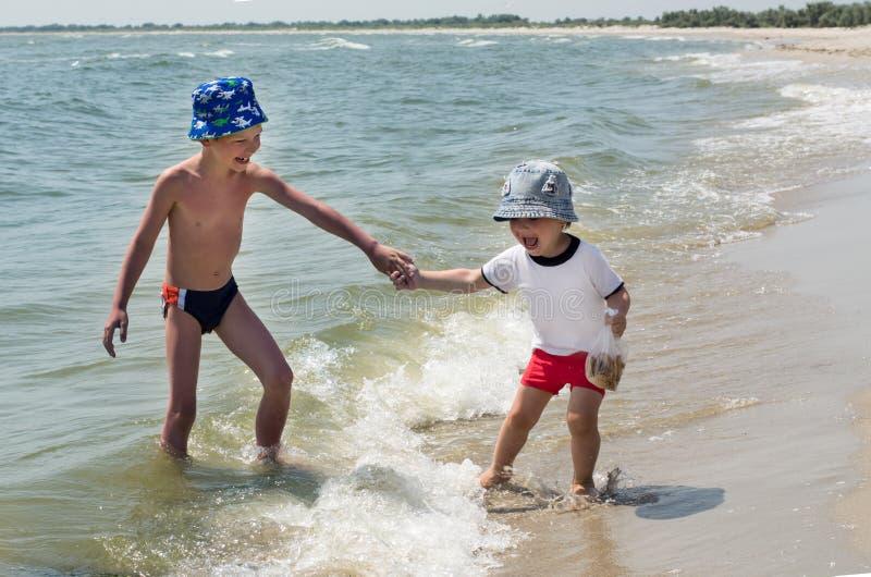 O irmão mais velho joga na praia com seu irmão mais novo, ondas, crianças felizes foto de stock