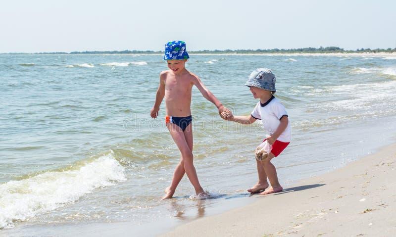 O irmão mais velho joga na praia com seu irmão mais novo, ondas, crianças felizes foto de stock royalty free