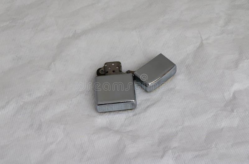 O isqueiro do metal abre o isolado da tampa no fundo do Livro Branco é um dispositivo que produza uma chama pequena foto de stock