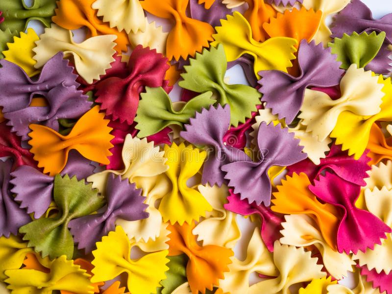 O italiano coloriu a massa secada do farfalle, um teste padrão do fundo fotografia de stock