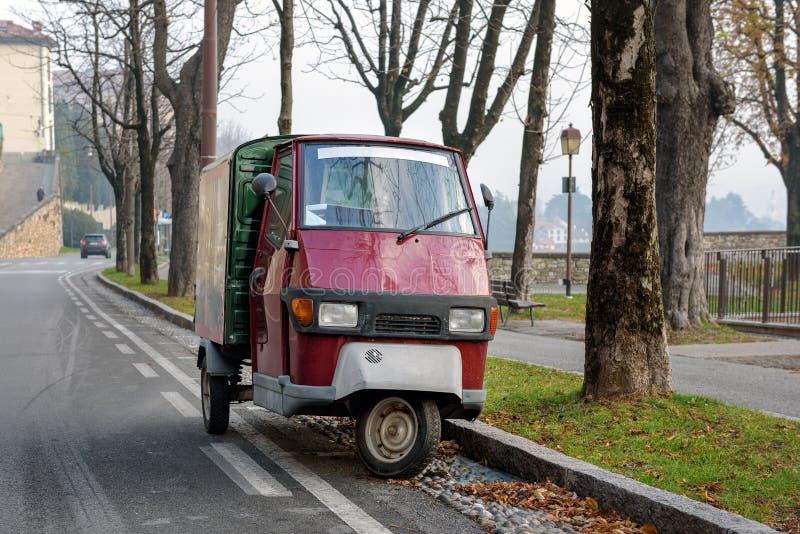 O italiano tradicional três roda o macaco de Piaggio do carro que fica estacionado na rua foto de stock