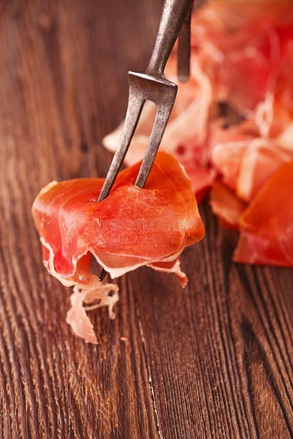 O jamon espanhol curou a carne na grande forquilha da carne do vintage imagem de stock royalty free