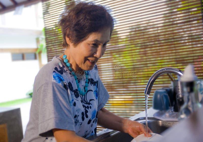 O japonês asiático feliz e doce superior aposentou-se, mulher que cozinha em fotografia de stock royalty free