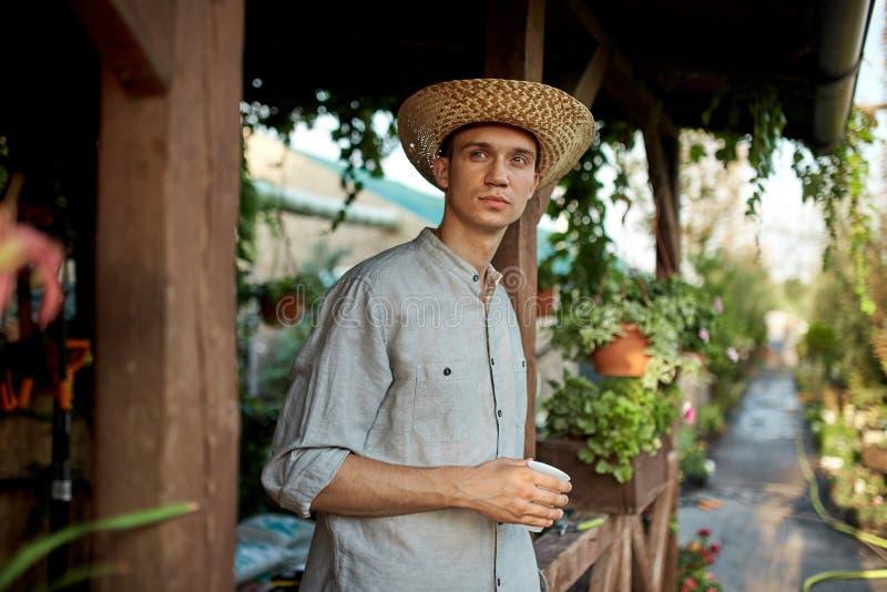 O jardineiro do indivíduo em um chapéu de palha está estando com vidro plástico em sua mão ao lado de uma varanda de madeira no b foto de stock royalty free