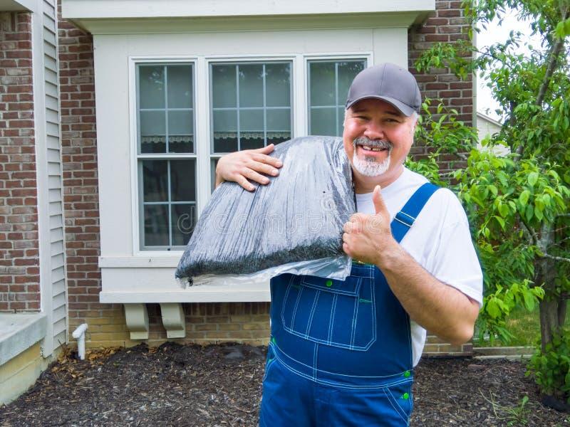 O jardineiro feliz ou ou o jardim prestam serviços de manutenção ao trabalhador fotografia de stock royalty free