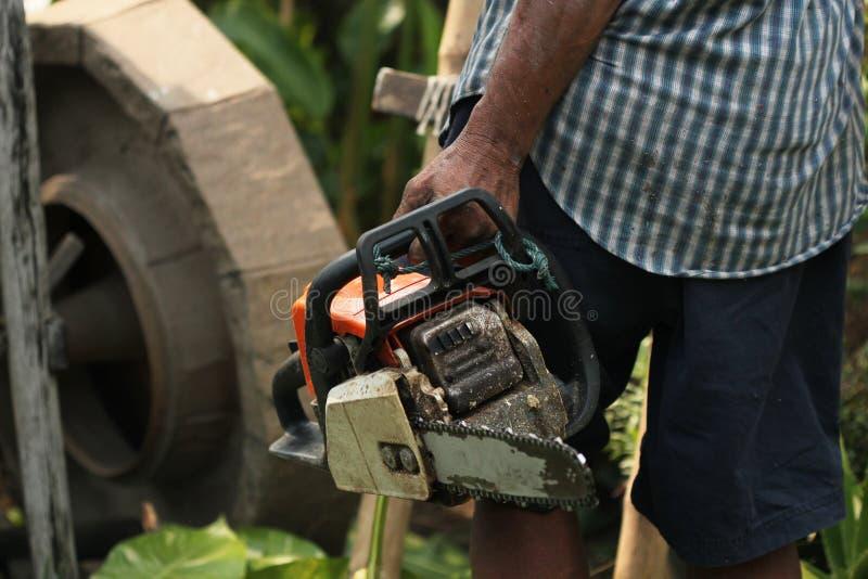 O jardineiro idoso do homem forte está guardando uma serra de cadeia resistente ao aparar e ao cortar grandes árvores no trabalho fotografia de stock royalty free