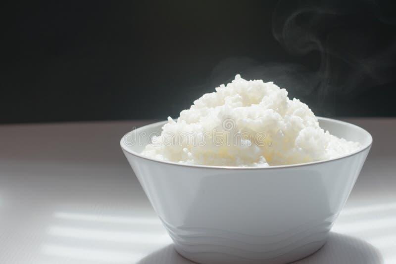 O jasmim cozinhou o revestimento do arroz apenas cozinhado pelo tempo do café da manhã, na bacia branca no fundo branco e preto imagens de stock royalty free
