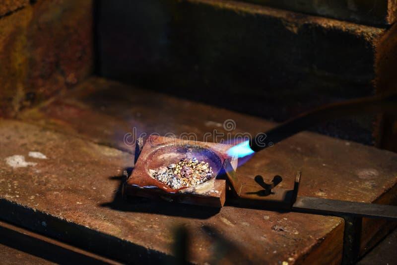 O joalheiro está derretendo grânulo do ouro e da prata em um cadinho com a fotografia de stock royalty free