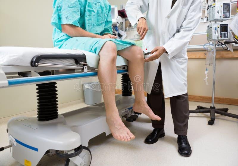 O joelho do paciente de exame do neurologista com martelo imagens de stock royalty free