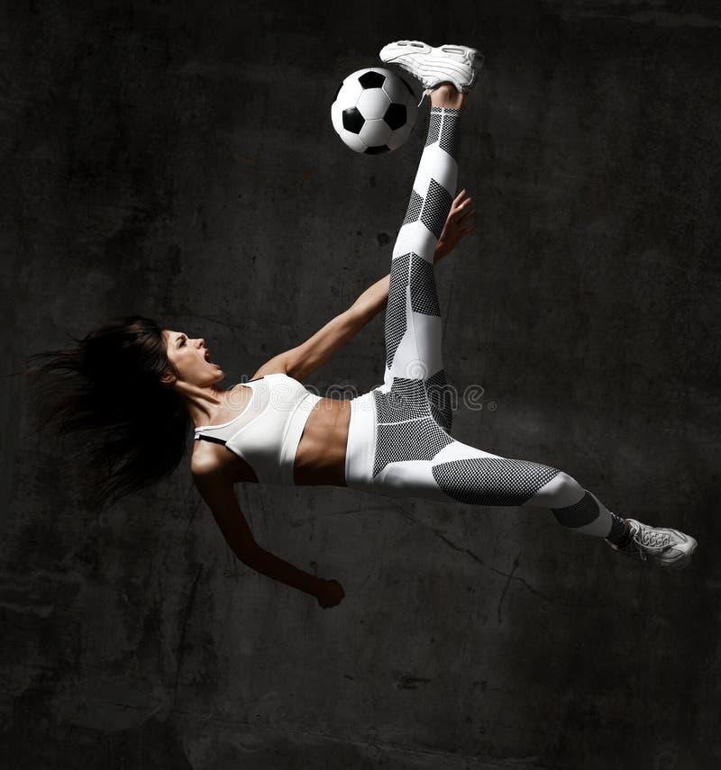O jogador da mulher do futebol salta e bate a bola que grita gritar na parede concreta do sótão imagem de stock royalty free