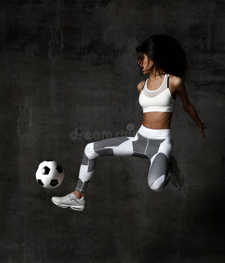 O jogador da mulher do futebol salta e bate a greve da bola no meio na parede concreta do sótão imagem de stock