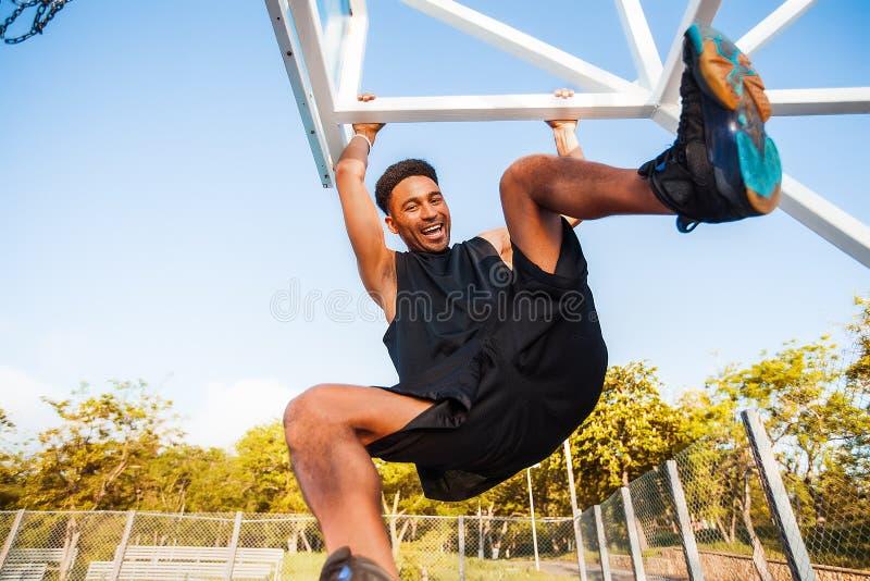 O jogador de basquetebol pendura na borda equipamento do esporte, competições de esporte foto de stock