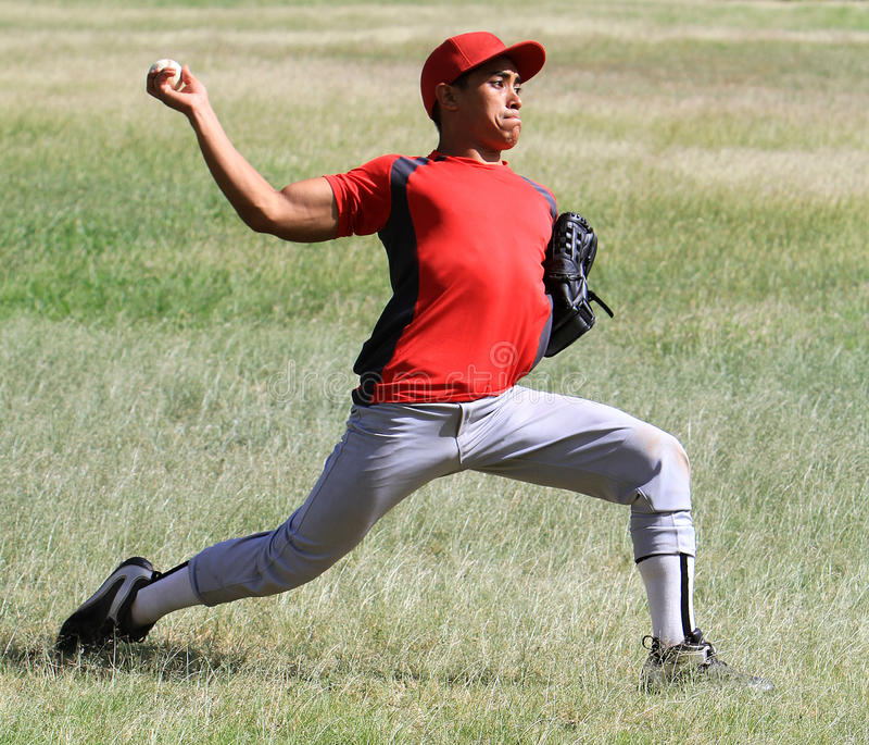 O jogador de beisebol joga a esfera abaixo da linha foto de stock royalty free