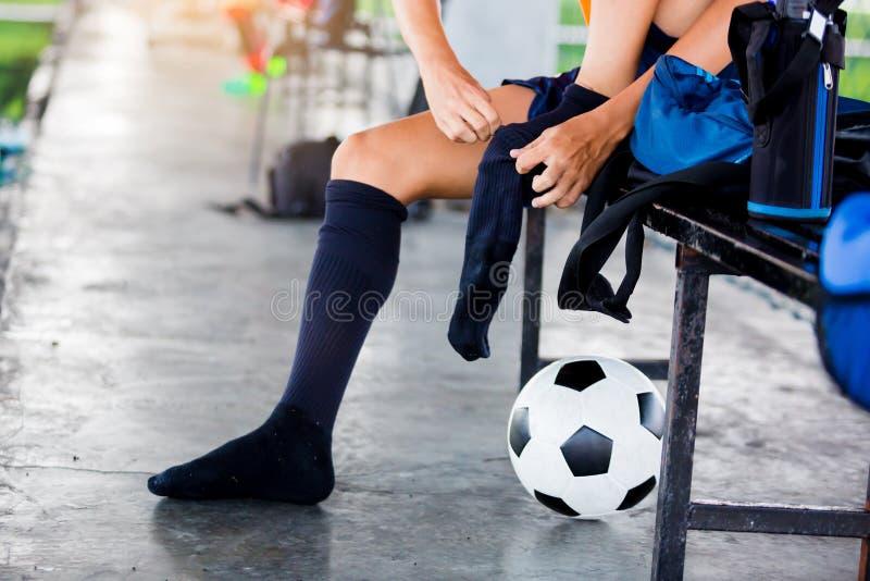 O jogador de futebol é de assento e de colocação a peúga preta do esporte fotografia de stock royalty free