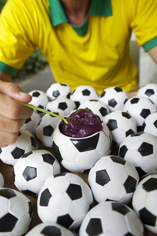 O jogador de futebol brasileiro come Acai com futebóis fotos de stock royalty free
