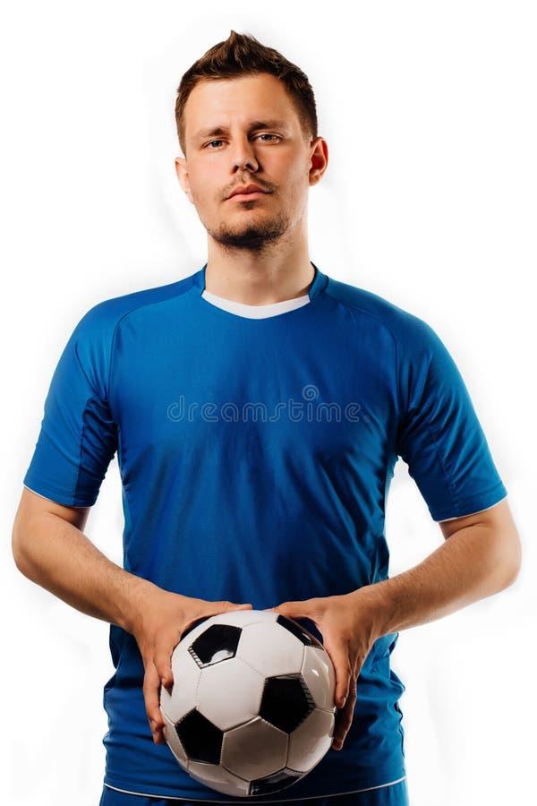 O jogador de futebol considerável novo realiza na bola de futebol das mãos que levanta no branco isolado imagens de stock