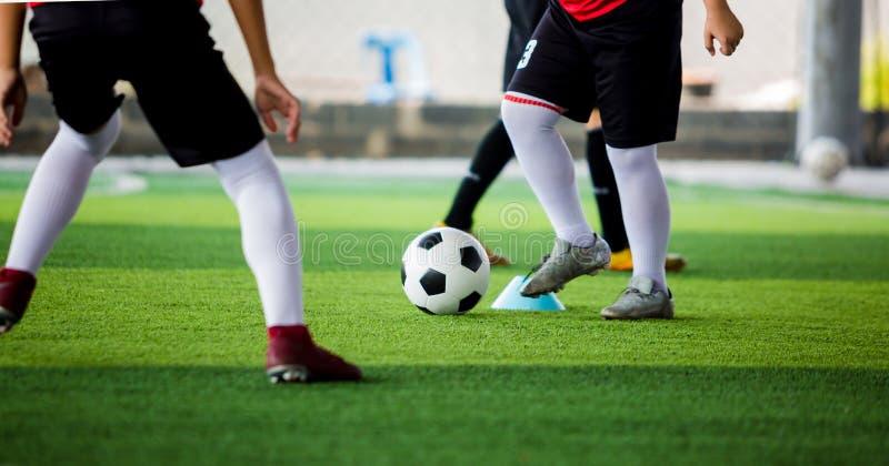 O jogador de futebol da criança pôs as sapatas brancas do esporte que movimentam-se e a bola de controle para ir a outros jogador imagem de stock