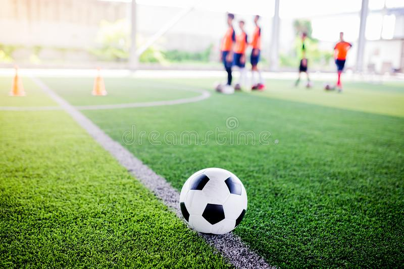O jogador de futebol das mulheres p?s sapatas pretas e corrida do esporte para a bola do tiro ao objetivo sobre o relvado artific imagem de stock