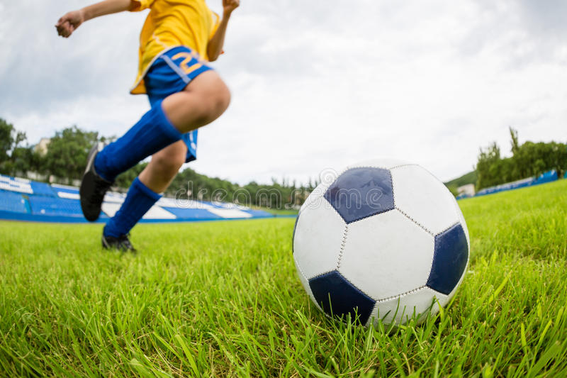 O jogador de futebol do menino bate a bola foto de stock royalty free