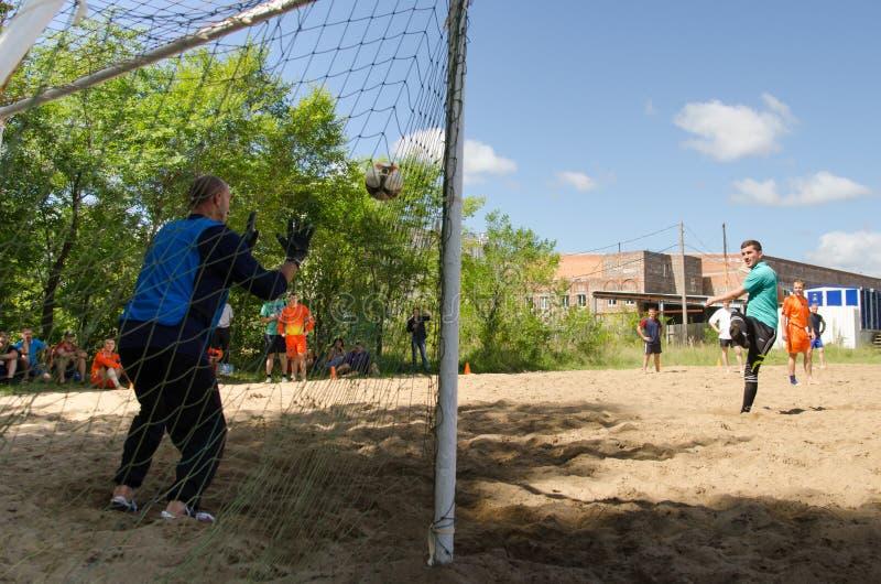 O jogador de futebol está no objetivo no campeonato amador do futebol da praia foto de stock royalty free