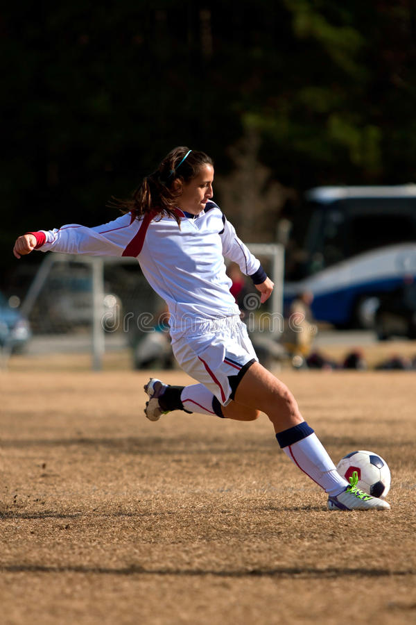 O jogador de futebol fêmea prepara-se para retroceder a esfera imagens de stock