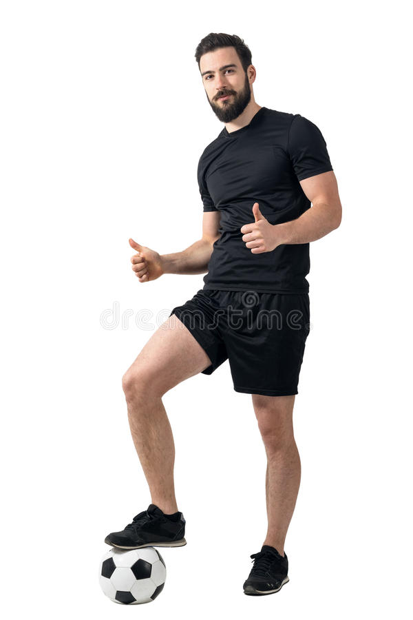 O jogador de futebol que está na bola com o um pé que mostra os polegares levanta o gesto foto de stock