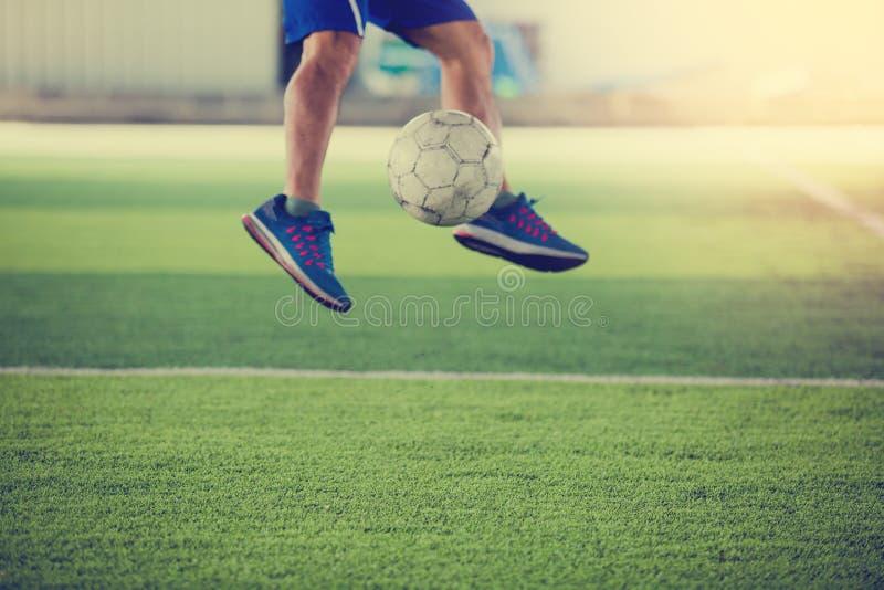 O jogador de futebol salta e dispara na bola ao objetivo no relvado artificial imagem de stock