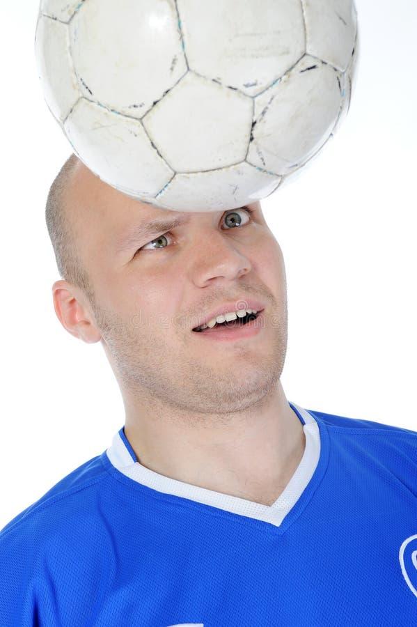 O jogador de futebol toma a cabeça da esfera. fotos de stock