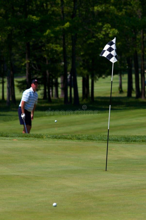 O jogador de golfe bate sua esfera de golfe fotografia de stock
