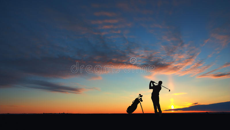 O jogador de golfe do homem bateu a bola ao ar mostrado em silhueta fotos de stock royalty free
