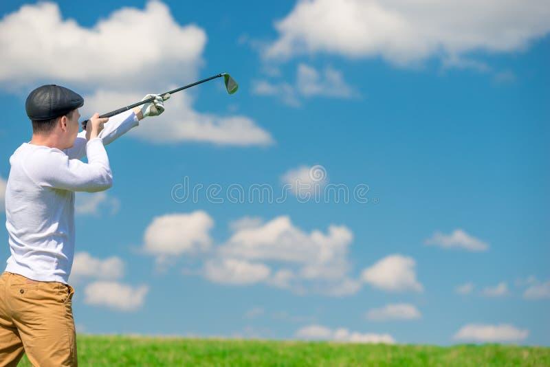O jogador de golfe está apontando com um clube de golfe, disparando imagens de stock