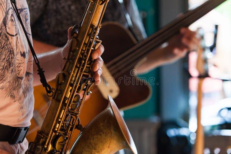 O jogador de saxofone do conteúdo está jogando um solo do jazz em um bar imagem de stock