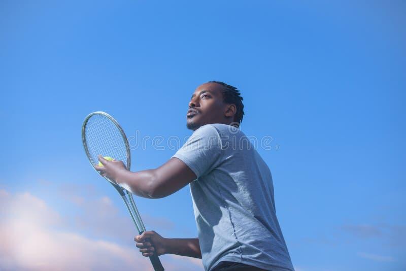 O jogador de tênis com bola e raquete contra o fundo do céu prepara-se para servir a bola fotos de stock royalty free