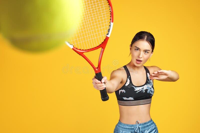 O jogador de tênis desportivo bonito da jovem mulher disparou na bola com a raquete vermelha sobre o fundo amarelo fotografia de stock