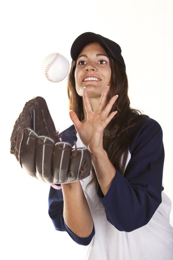 O jogador do basebol ou do softball da mulher trava uma esfera fotos de stock
