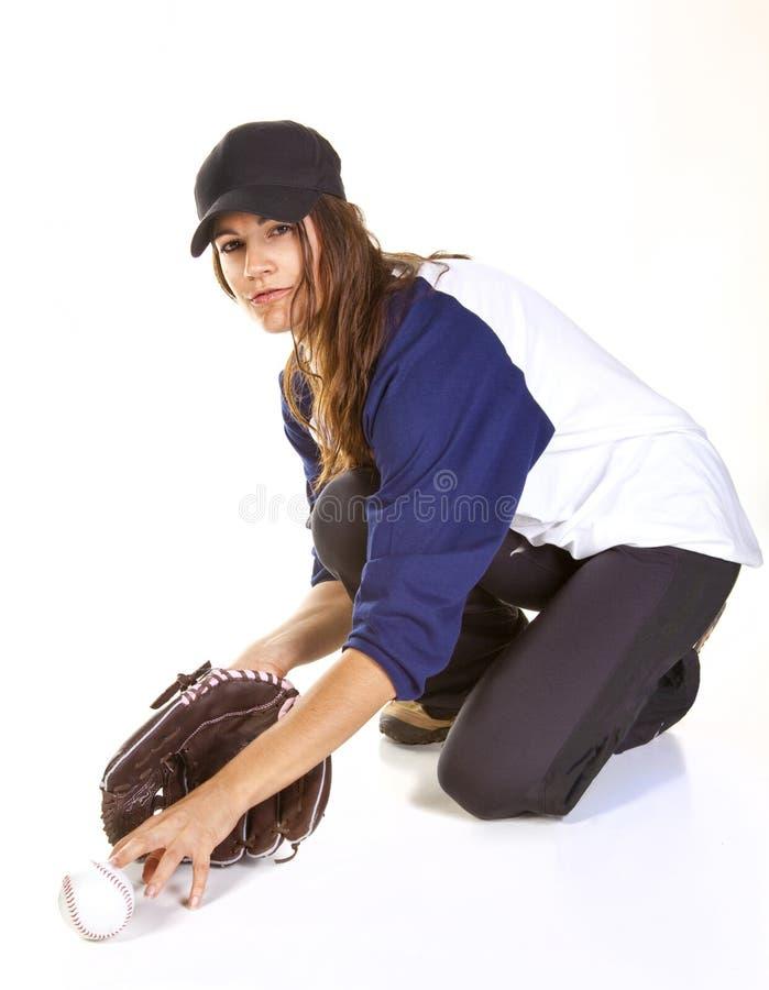 O jogador do basebol ou do softball da mulher trava uma esfera foto de stock royalty free