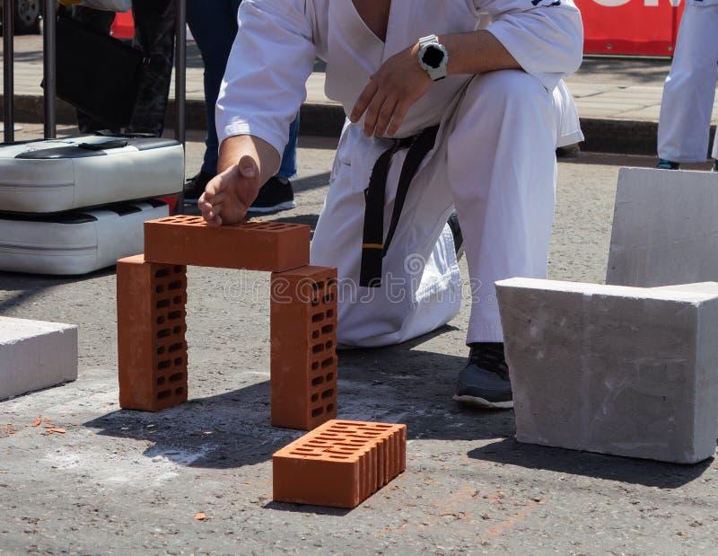 O jogador do karaté em um evento desportivo quebra um tijolo com sua mão foto de stock