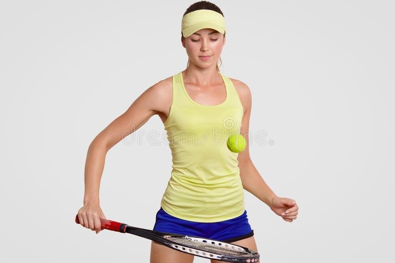 O jogador profissional do tênis fêmea novo atrativo bateu a bola de tênis com raquete, trens no gym, vestiu a faixa, o short e o  foto de stock