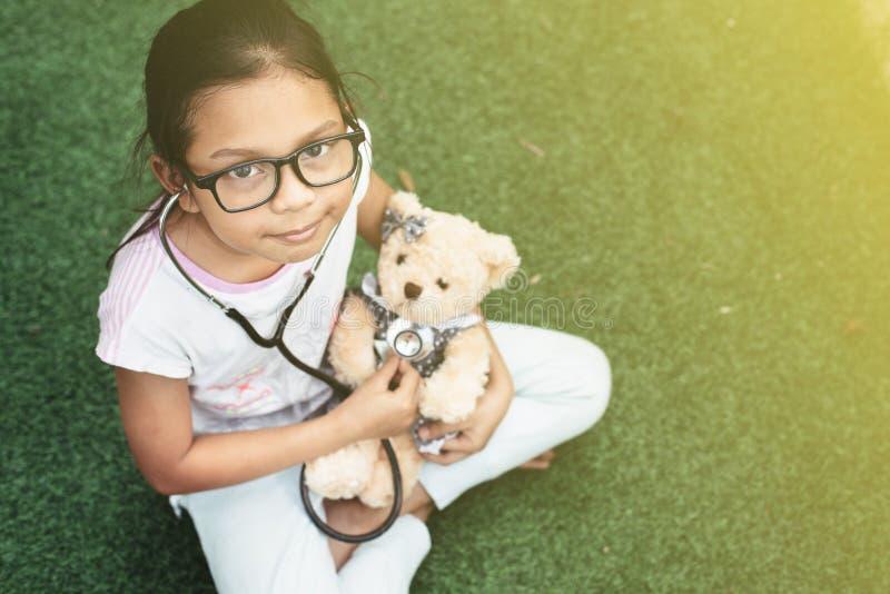 O jogo asiático pequeno novo da menina finge ser um doutor eaxamine da moça seu urso de peluche com estetoscópio fotografia de stock royalty free