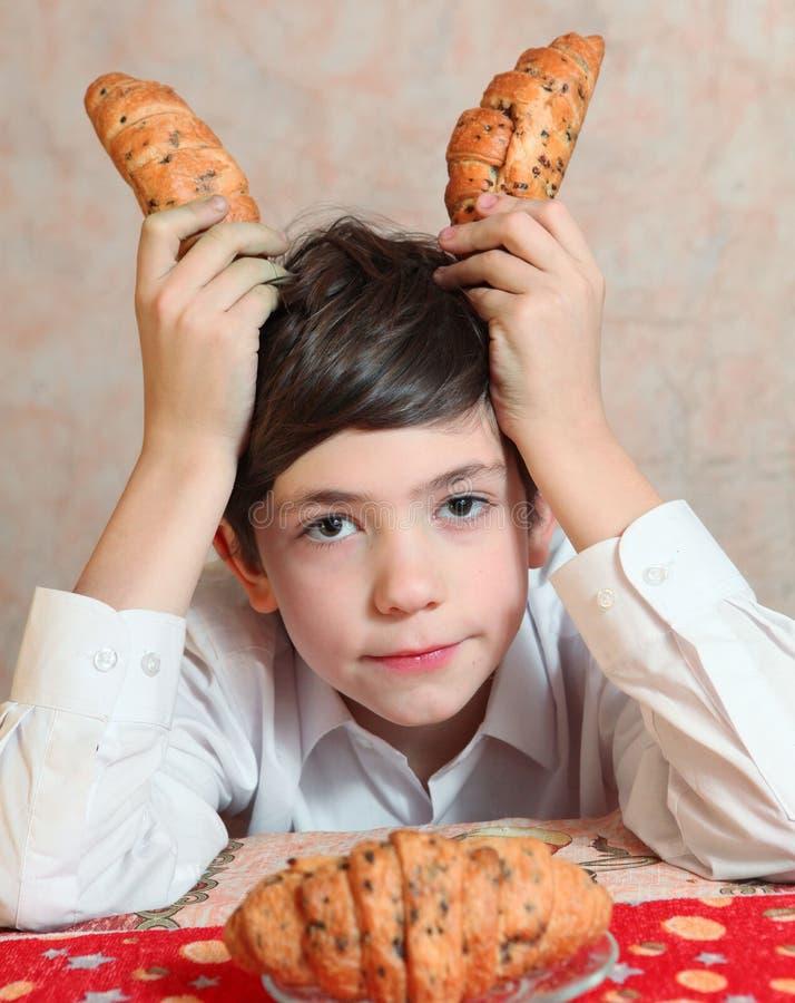 O jogo considerável do menino do preteen com croissan imagina seu um carneiro imagem de stock royalty free